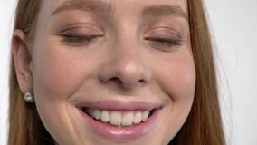 Twarz młodego cukierki spokoju imbirowa dziewczyna otwiera oczy, oglądający przy kamerą, ono uśmiecha się, biały tło zbiory wideo