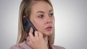Twarz młody rozochocony bizneswoman opowiada na telefonie komórkowym na gradientowym tle zdjęcie wideo
