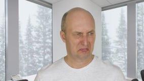 Twarz obrzydzał mężczyzna z niechęcią na tła okno z widokiem na opadzie śniegu w lesie zdjęcie wideo