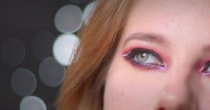 Twarz portret blondynka model z jaskrawym makijażem jest uwodzicielski flirtować z kamerą na bokeh tle zbiory