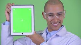 Twarz szczęśliwa łysa wielo- etniczna mężczyzna lekarka z ochronnymi eyeglasses pokazuje cyfrową pastylkę zbiory