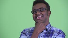 Twarz szczęśliwy młody Afrykański modnisia mężczyzna z eyeglasses myśleć zbiory