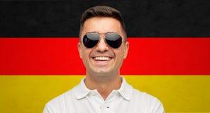 Twarz uśmiechnięty mężczyzna w okularach przeciwsłonecznych nad niemiec flaga fotografia stock
