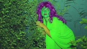 Twarz zielona czarownica od gąszczy na brzeg jezioro przy półmrokiem i delikatnie patrzeć wokoło zdjęcie wideo