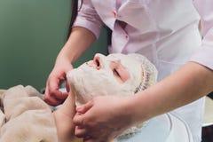 Twarzowe procedury ?adna wykwalifikowana kosmetyczka zdejmuje mask? podczas gdy robi? pi?kno procedurze zdjęcie stock