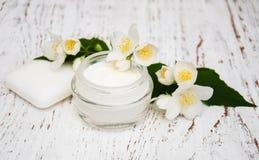 Twarzy i ciała śmietanki moisturizers z jaśminem kwitną na białym w obrazy stock