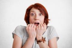 Twarzy ludzkich emocj i wyrażeń pojęcie Okaleczająca młoda kobieta z imbirowym krótkim włosy, utrzymuje ręki na podbródku, spojrz zdjęcia stock