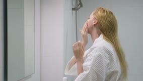 Twarzy opieki pojęcie Kobieta stosuje kosmetyczną płukankę brać opiekę skóra w łazience Ranek higiena zbiory wideo