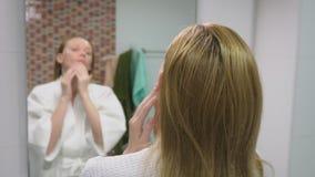 Twarzy opieki pojęcie Kobieta stosuje kosmetyczną płukankę brać opiekę skóra w łazience Ranek higiena zdjęcie wideo