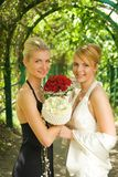Twe girls with a flowers. In green alley Royalty Free Stock Images