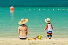 Twee éénjarigen peuter het spelen met moeder op strand Royalty-vrije Stock Foto's