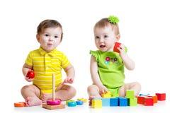 Twee aanbiddelijke jonge geitjes die met speelgoed spelen Peutersmeisje Stock Afbeelding