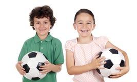 Twee aanbiddelijke kinderen met voetbalballen Stock Afbeelding