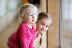 Twee aanbiddelijke kleine zusters door het venster Royalty-vrije Stock Fotografie