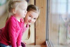 Twee aanbiddelijke kleine zusters door het venster Stock Foto