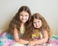 Twee aanbiddelijke meisjes die met lang haar samen koesteren Royalty-vrije Stock Afbeeldingen