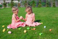 Twee aanbiddelijke meisjes die met Paaseieren spelen Stock Afbeeldingen