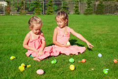 Twee aanbiddelijke meisjes die met Paaseieren spelen Stock Foto's