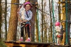 Twee aanbiddelijke meisjes in helm in een kabelpark in het hout royalty-vrije stock afbeeldingen