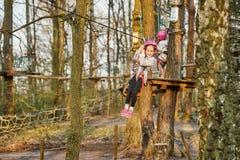 Twee aanbiddelijke meisjes in helm in een kabelpark in het hout stock foto
