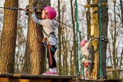 Twee aanbiddelijke meisjes in helm in een kabelpark in het hout royalty-vrije stock foto's