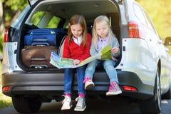 Twee aanbiddelijke meisjes klaar om op vakanties met hun ouders te gaan Jonge geitjes die in een auto zitten die een kaart onderz Royalty-vrije Stock Afbeeldingen