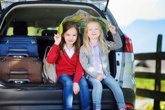 Twee aanbiddelijke meisjes klaar om op vakanties met hun ouders te gaan Jonge geitjes die in een auto zitten die een kaart onderz Stock Afbeeldingen