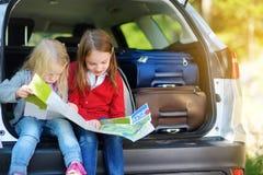 Twee aanbiddelijke meisjes klaar om op vakanties met hun ouders te gaan Jonge geitjes die in een auto zitten die een kaart onderz Stock Foto