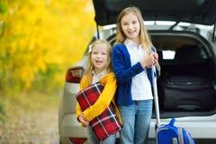 Twee aanbiddelijke meisjes met een koffer die op vakanties met hun ouders gaan Twee jonge geitjes die vooruit voor een een wegrei Royalty-vrije Stock Foto's