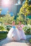 Twee aanbiddelijke meisjes met mooie boeketten van rozen in handen gaan naar het huwelijk Stock Foto's