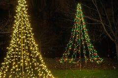 Twee aangestoken Kerstbomen bij vakantielicht tonen royalty-vrije stock foto's