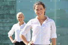 Twee aantrekkelijke bedrijfsvrouwen die buiten stellen Royalty-vrije Stock Afbeelding