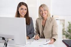 Twee aantrekkelijke bedrijfsvrouwenzitting samen in een team in Stock Foto's