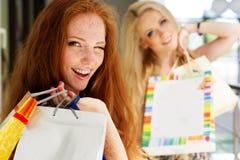 Twee aantrekkelijke gelukkige meisjes die uit winkelen Royalty-vrije Stock Afbeelding
