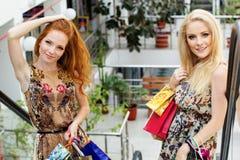 Twee aantrekkelijke gelukkige meisjes die uit winkelen Stock Afbeeldingen