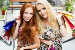 Twee aantrekkelijke gelukkige meisjes die uit winkelen Royalty-vrije Stock Afbeeldingen