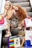 Twee aantrekkelijke gelukkige meisjes die uit winkelen Stock Fotografie