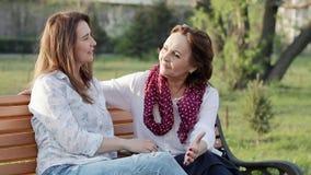 Twee aantrekkelijke gelukkige oude en op middelbare leeftijd vrouwenmeisjes die in het park babbelen stock video