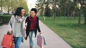 Twee aantrekkelijke gemengde rasvrouwen die en hebben pret terwijl het lopen onderaan het park met het winkelen zakken dansen Gel royalty-vrije stock fotografie