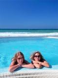 Twee aantrekkelijke jonge meisjes in een zwembad op het strand Stock Afbeeldingen