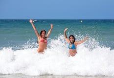 Twee aantrekkelijke jonge meisjesvrienden die in het overzees op vakantie spelen royalty-vrije stock fotografie