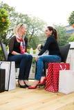 Twee aantrekkelijke jonge vrouwelijke vrienden die van een dagtocht genieten na het succesvolle winkelen Stock Afbeeldingen
