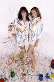Twee aantrekkelijke jonge vrouwen omvat in kleurrijke verf Royalty-vrije Stock Afbeeldingen