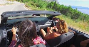 Twee aantrekkelijke meisjes die in convertibel met top down drijven stock video
