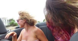 Twee aantrekkelijke meisjes die in convertibel met top down drijven en van de wind genieten stock video