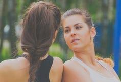 Twee aantrekkelijke meisjes die op de Speelplaats stellen Royalty-vrije Stock Foto's