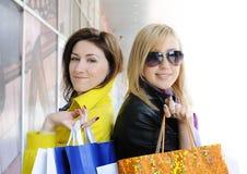 Twee aantrekkelijke meisjes die uit winkelen Stock Foto