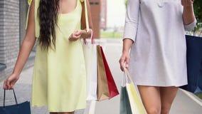 Twee aantrekkelijke meisjes lopen onderaan de straat en bespreken het winkelen na het winkelen 4K stock footage
