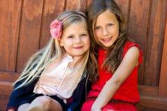 Twee aantrekkelijke meisjes naast houten muur. Stock Foto's