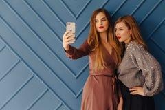Twee aantrekkelijke modieuze jonge meisjes met telefoon op eenvoudige aquaachtergrond royalty-vrije stock afbeeldingen